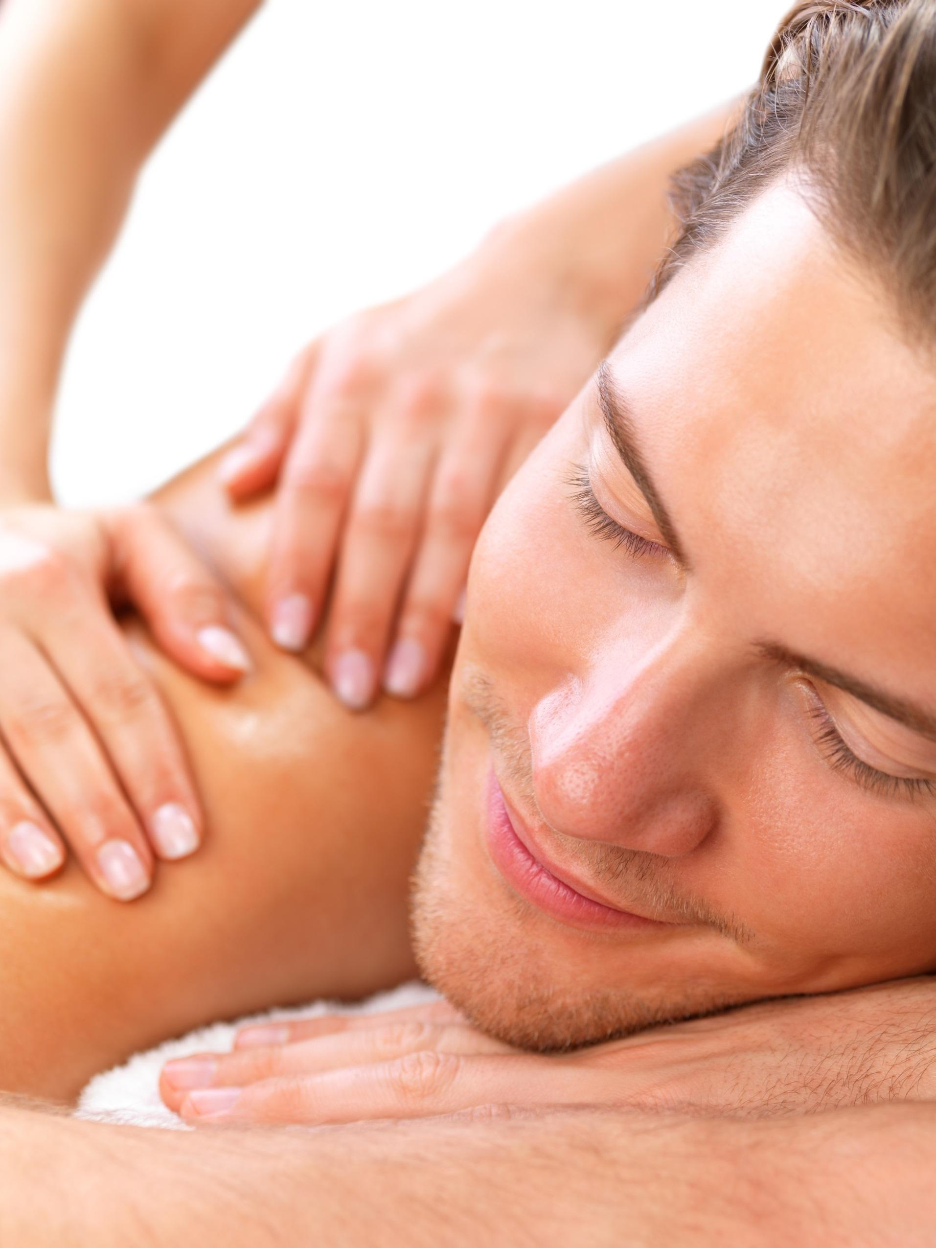 Close up portrait of a young smiling man getting shoulder massage from masseuse